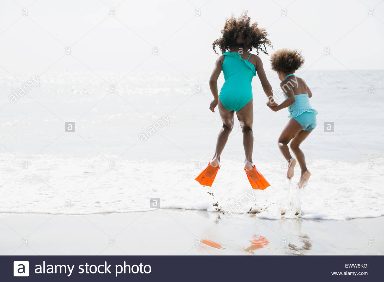 Sisters in bathing suits jumping in ocean surf - Stock Image