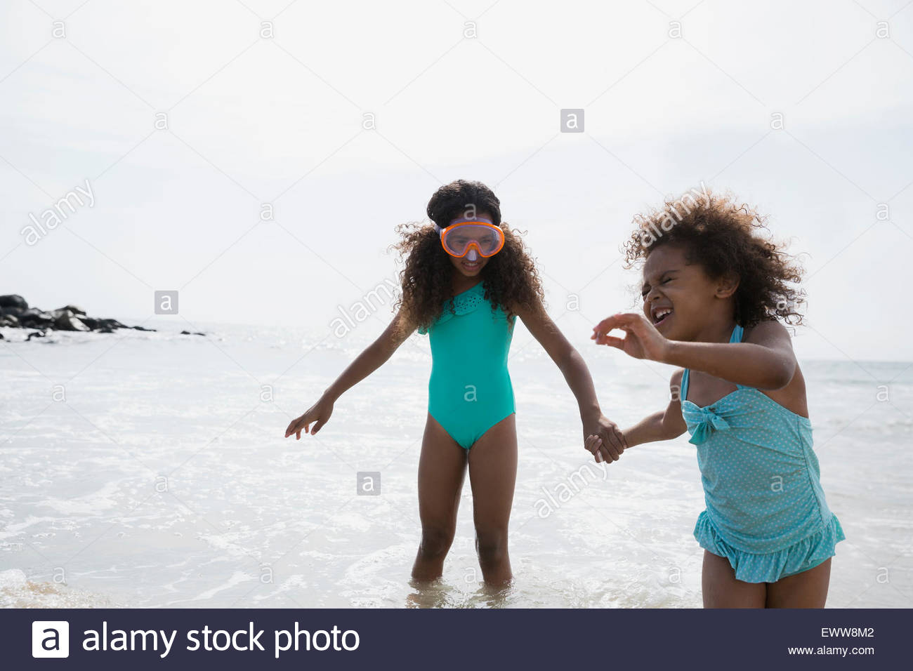 Sisters in bathing suits holding hands ocean surf - Stock Image