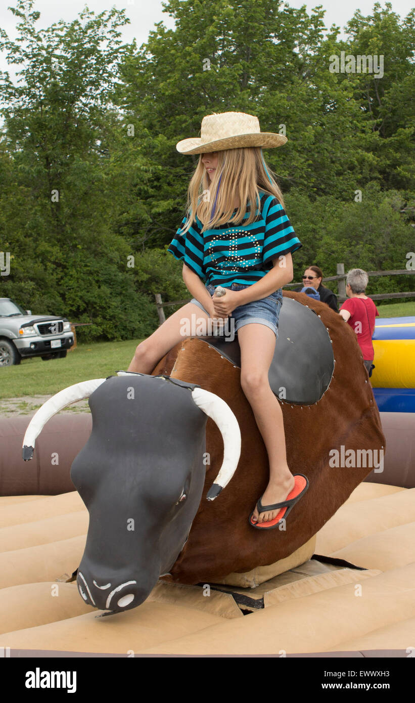 young-pre-teen-girl-rides-a-mechanical-bull-at-the-canada-day-celebrations-EWWXH3.jpg