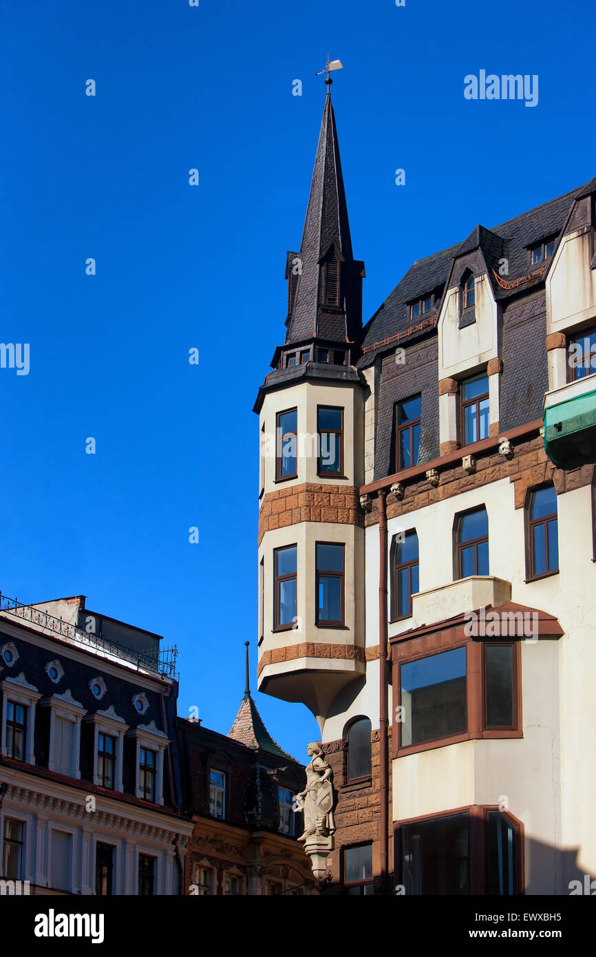Facades of old houses with spiers and weather vanes bas-relief of a woman in the center of Riga's Dome Square - Stock Image