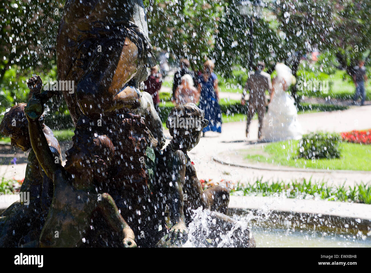 Wedding in the central park of Riga in the spray of the old fountain in summer day - Stock Image
