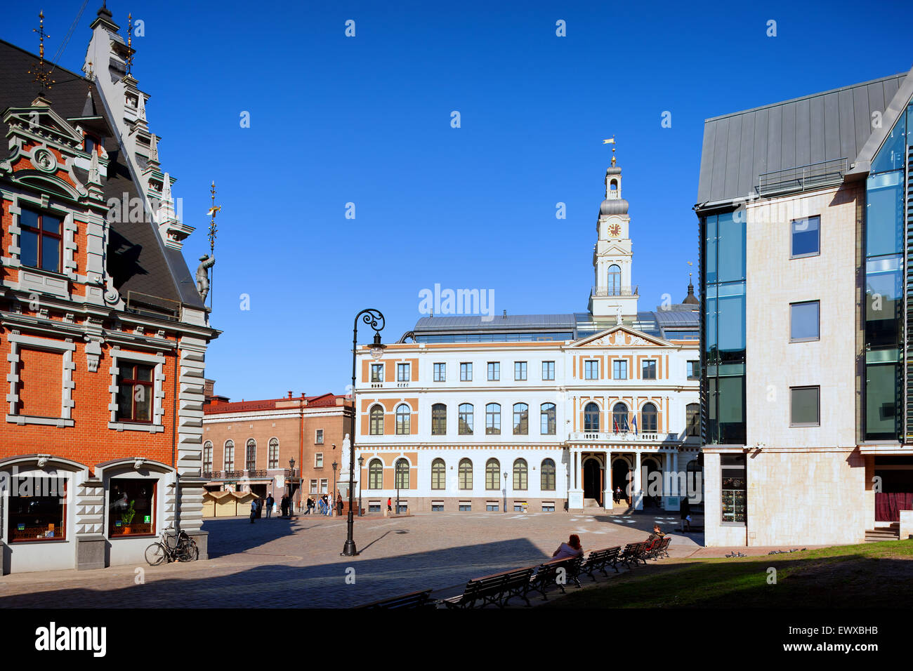 Town hall with clock and weather vane on the area and the House of Blackheads in Riga on a sunny spring day - Stock Image