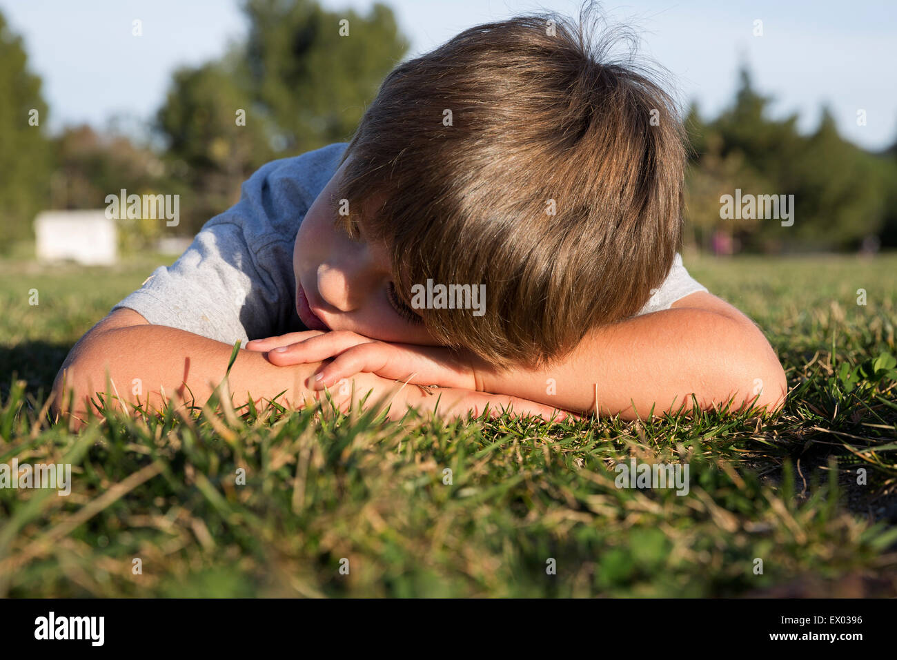 Sullen boy with head down lying on park grass - Stock Image