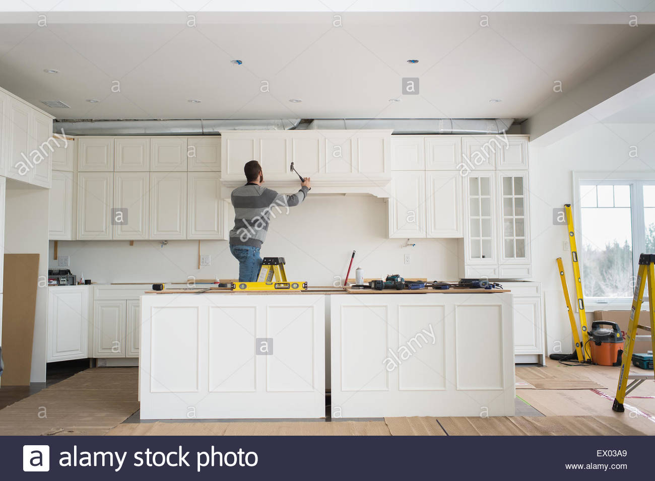 Carpenter installing kitchen cabinet Stock Photo: 84825169 - Alamy