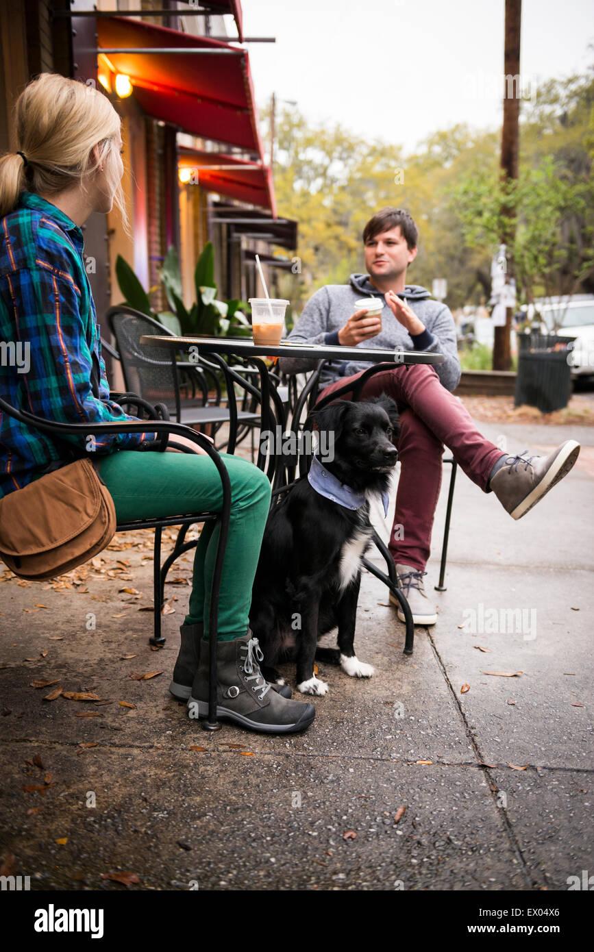 Couple with dog having coffee at sidewalk cafe, Savannah, Georgia, USA - Stock Image