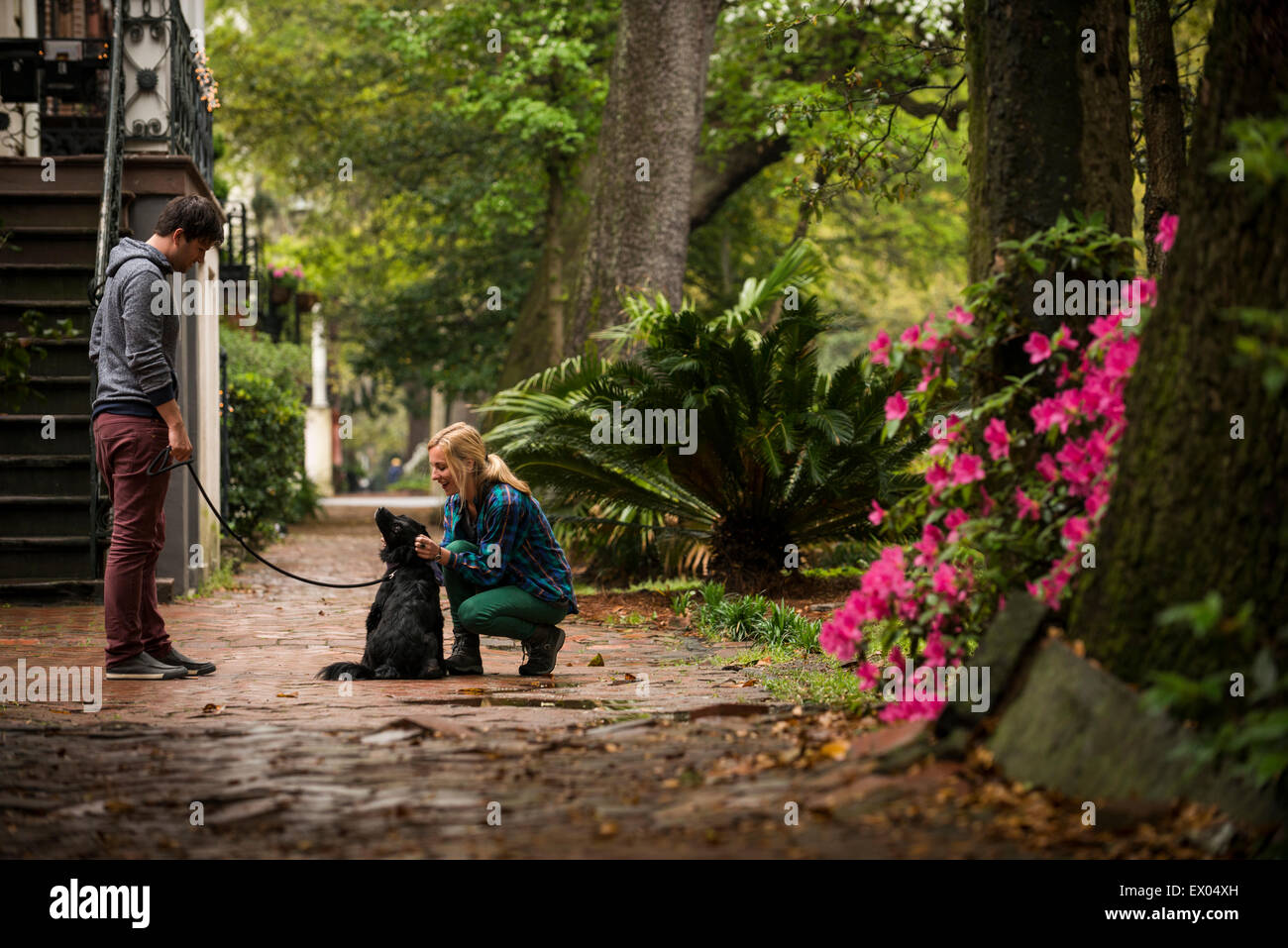 Couple with dog behind house, Savannah, Georgia, USA - Stock Image