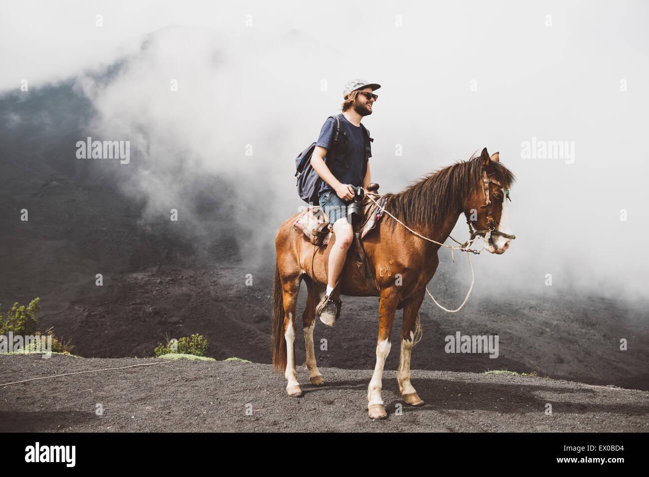 Young man horse trekking at Pacaya volcano, Antigua, Guatemala - Stock Image