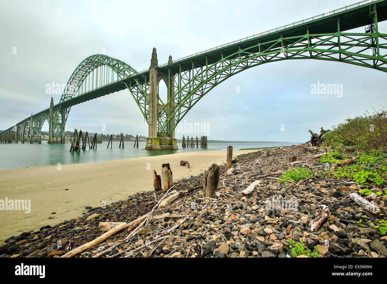 Wooden pylons, gravel and Yaquina Bay Bridge, Newport, Oregon USA - Stock Image