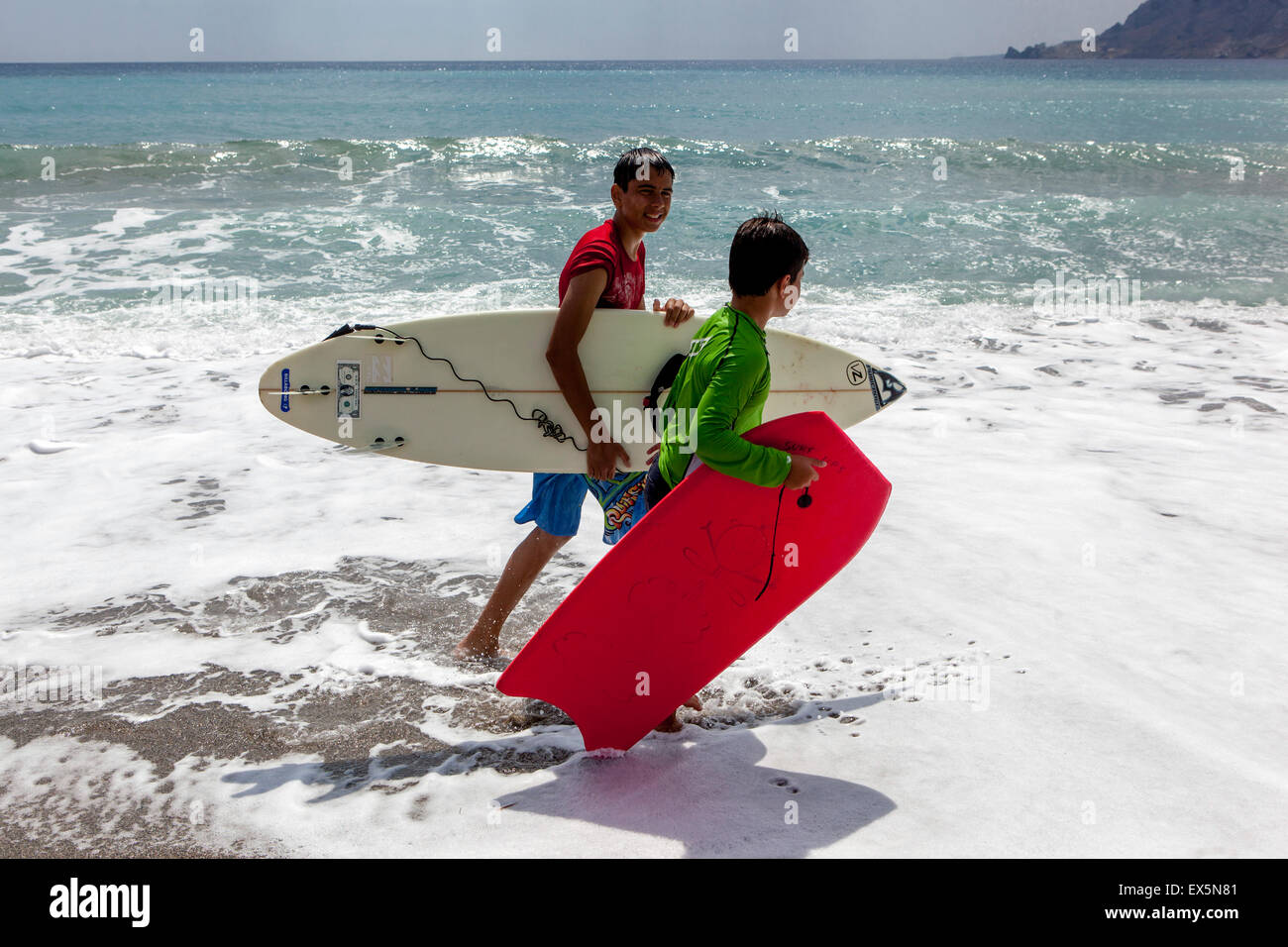 Two boys with surf boards, go on the beach, Plakias, Crete, Greek Island, Greece - Stock Image