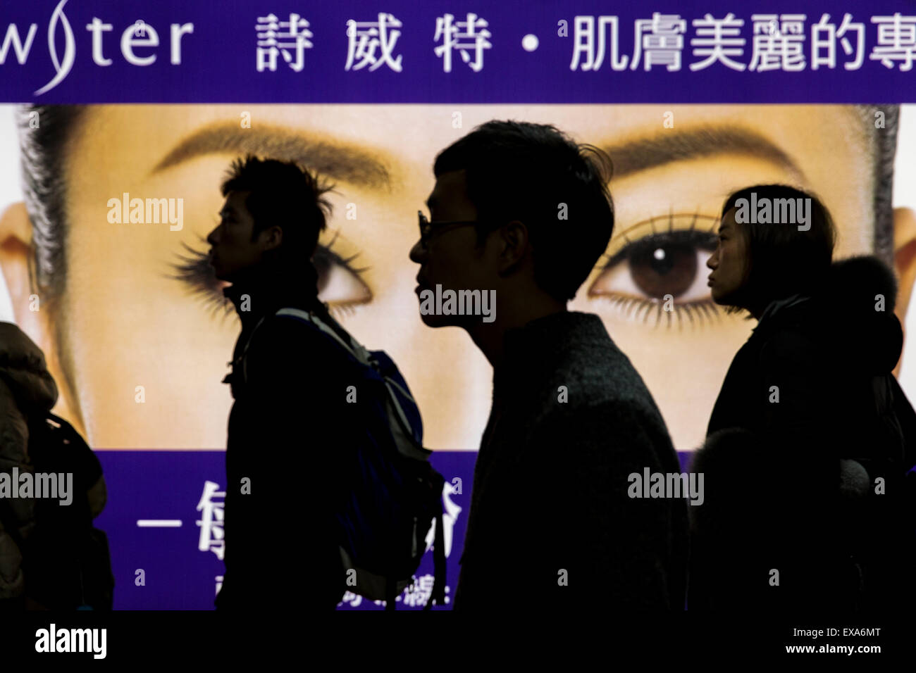 Asia, Taiwan, Taipei, Silhouette of passengers walking past illuminated billboard of Chinese woman's eyes inside Stock Photo