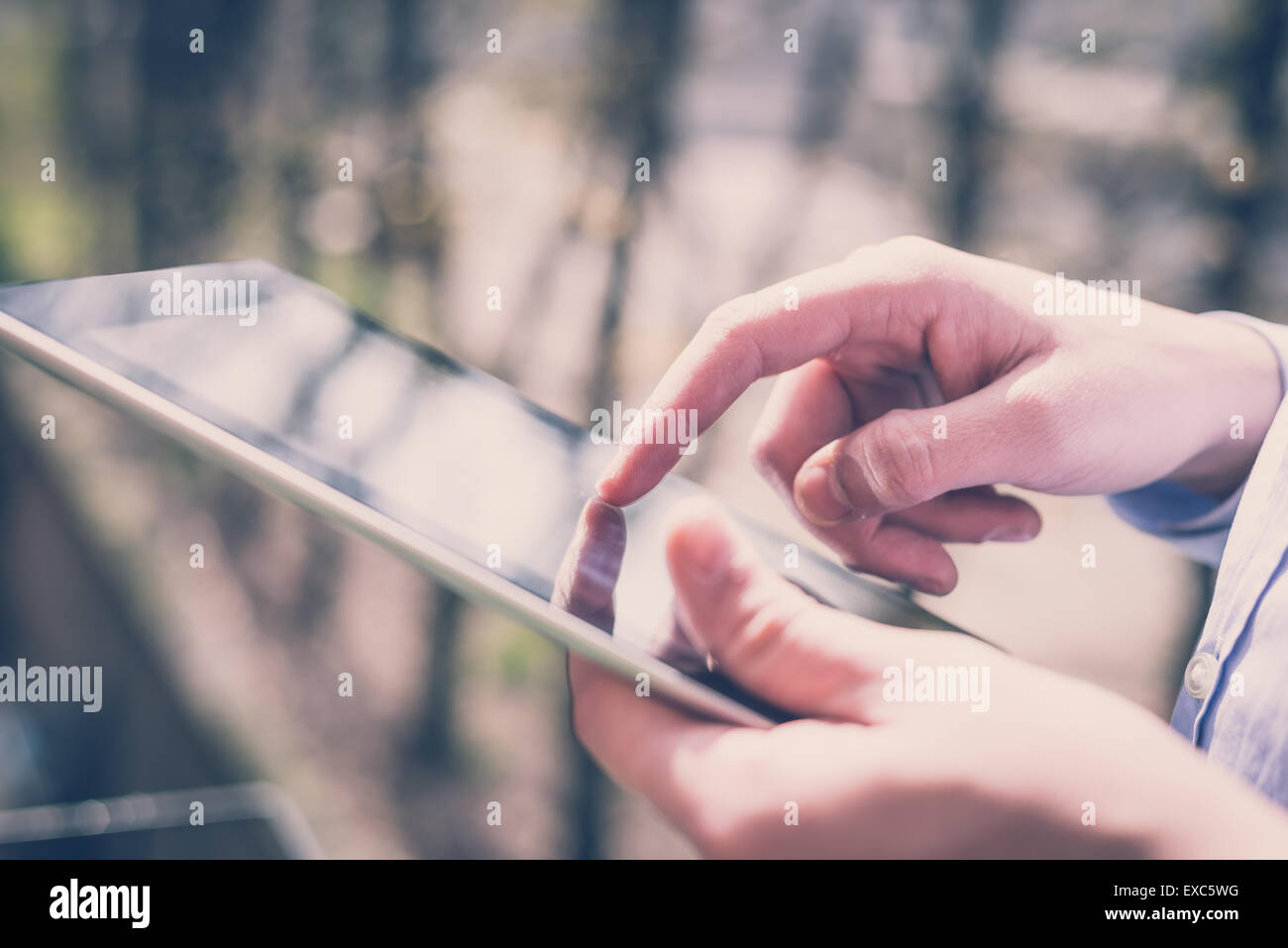 close up hands multitasking man using tablet connecting wifi - Stock Image