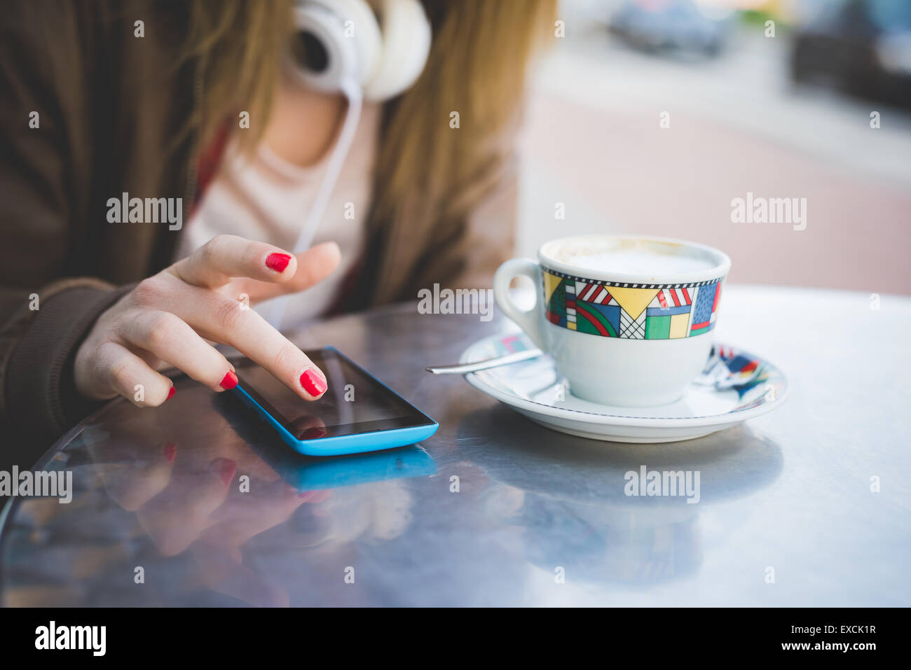 close up of woman hand using smartphone on a cafe bar table and cup of coffee - Stock Image