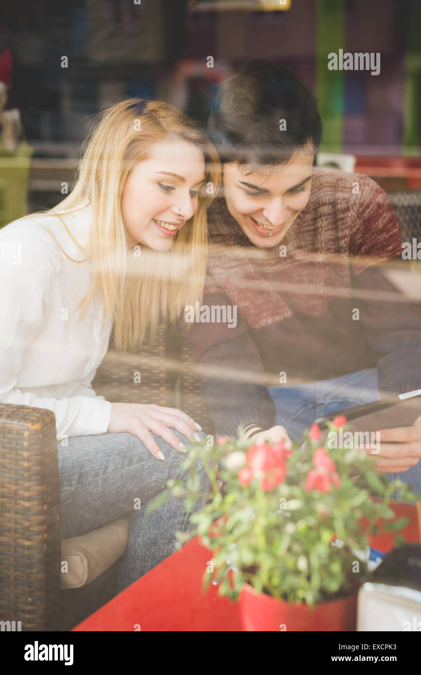 young beautiful couple lovers sitting at the bar using wireless tablet connected online - Stock Image