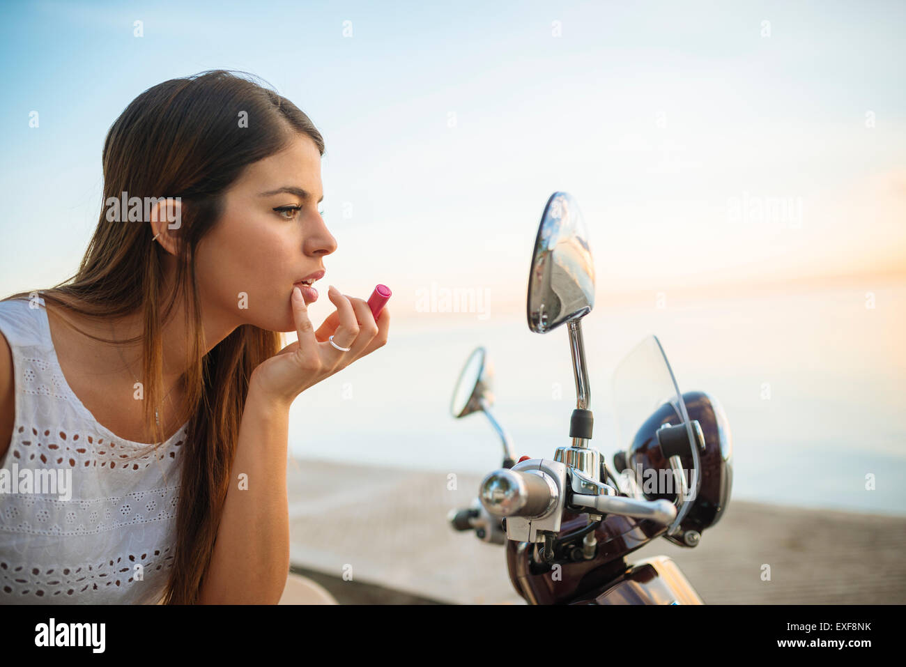 Young woman applying lipstick in motorcycle mirror, Manila, Philippines - Stock Image