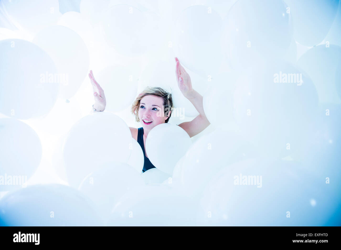 Globophobia: a happy smiling young woman girl alone in a cloud of hundreds of white balloons - having overcome her - Stock Image