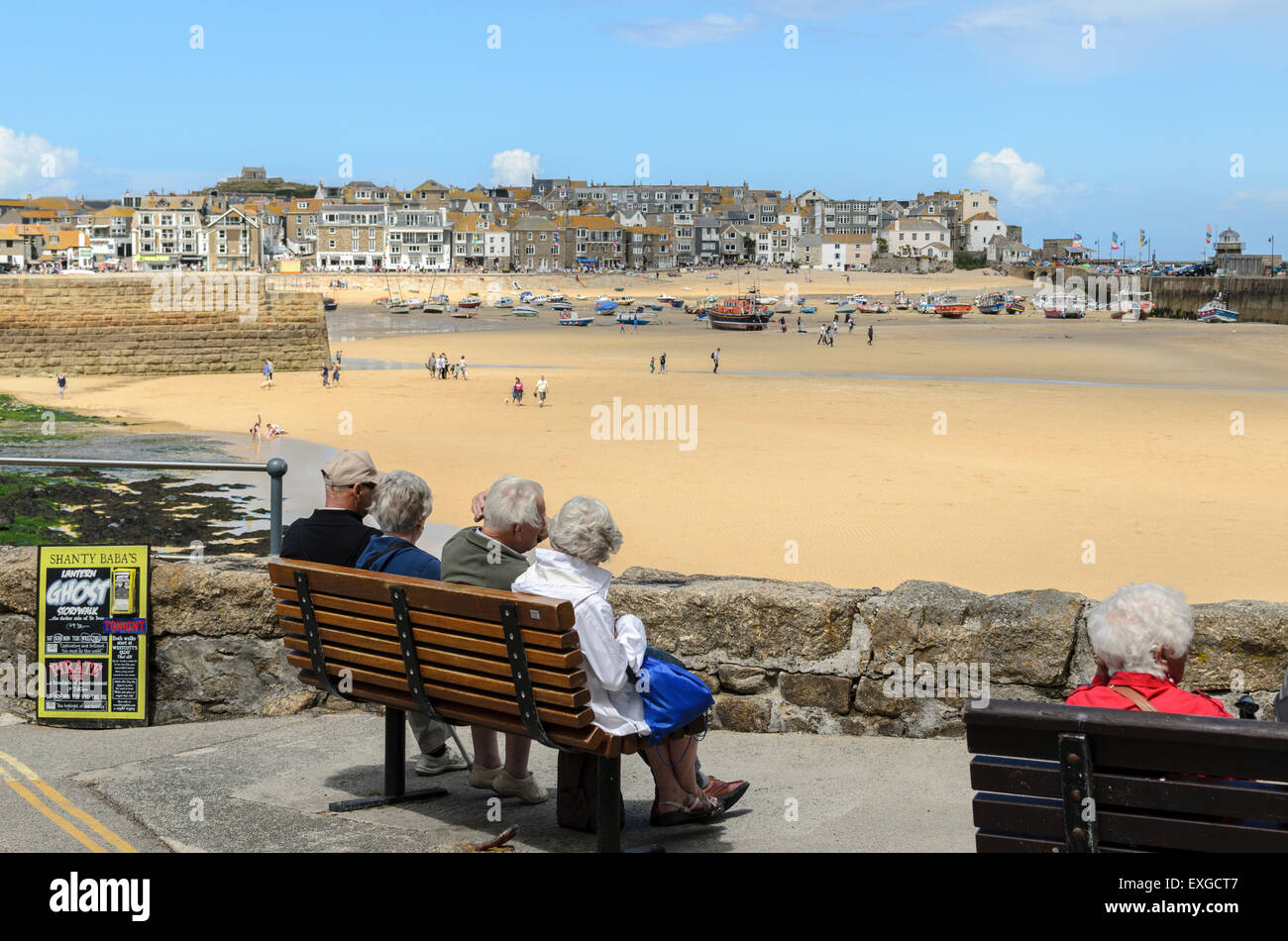 Senior Citizens sit at The Warren looking out at the harbour, St Ives, Cornwall. The town is popular with tourists - Stock Image