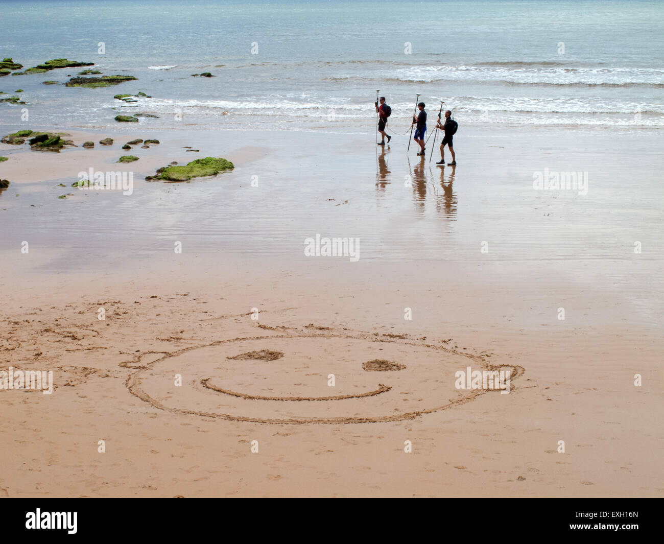 Sidmouth. A smiley face in the sand greets visitors to the beach beneath Jacobs Ladder, at Sidmouth, Devon. Stock Photo