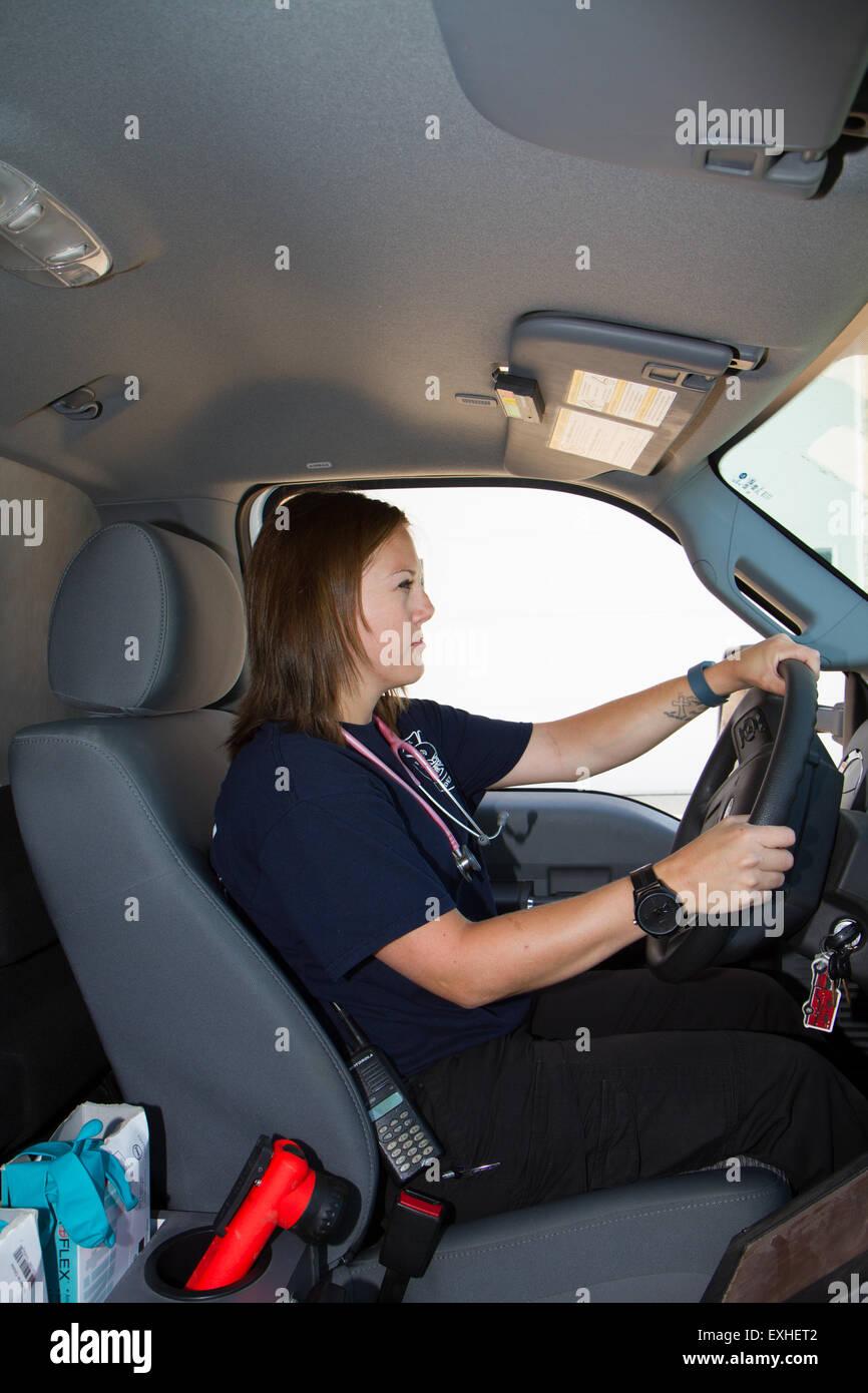 Female paramedic EMT using radio in ambulance. Rural volunteer fire department ambulance. Stock Photo