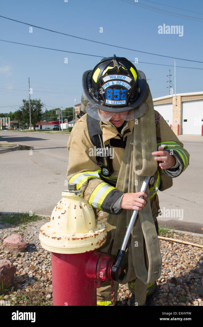 Female firefighter in rural volunteer fire department working with equipment. Stock Photo