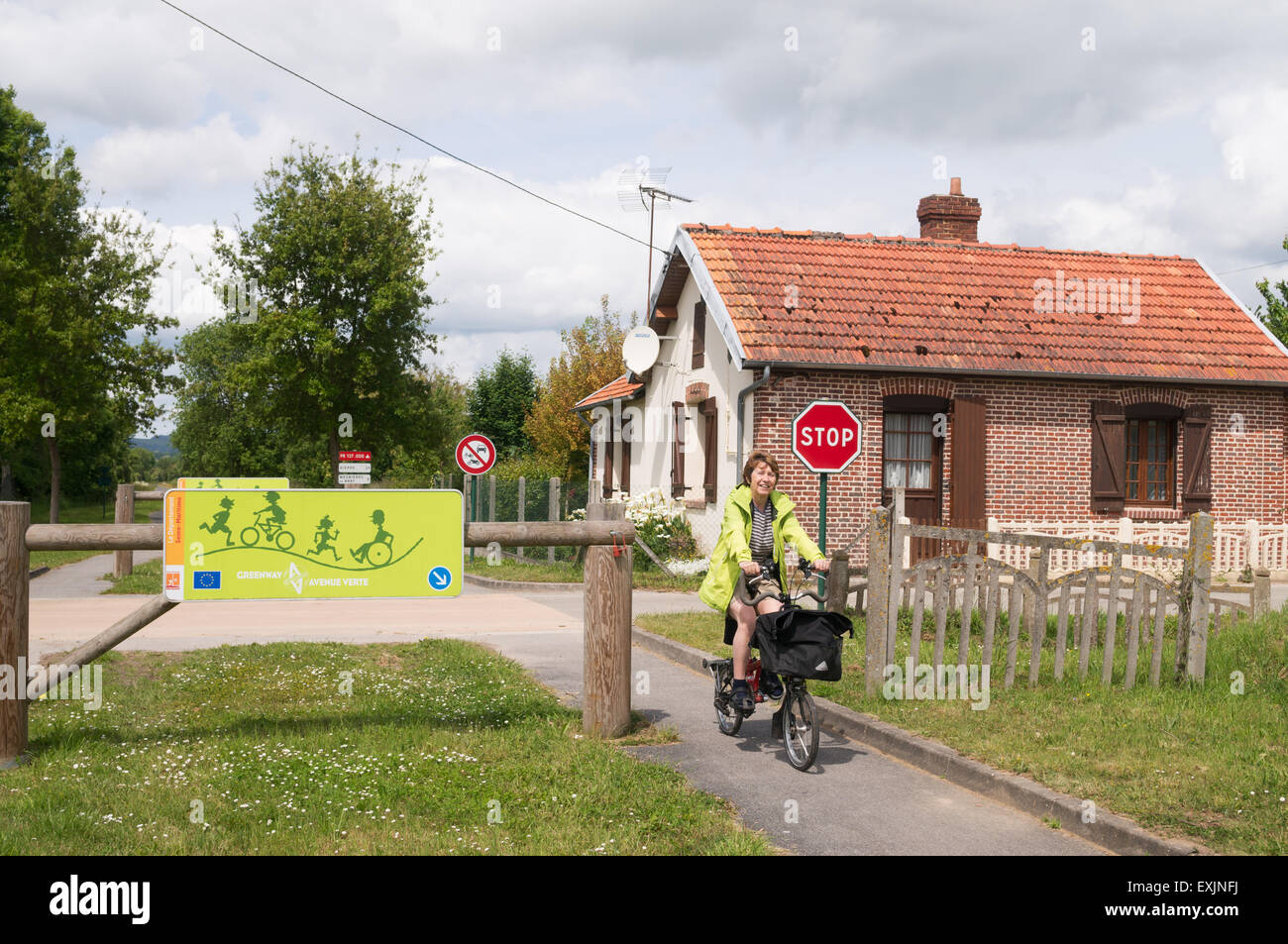 Smiling female cyclist riding a Brompton bike on the Greenway or Avenue Verte between Dieppe and Paris, France Stock Photo