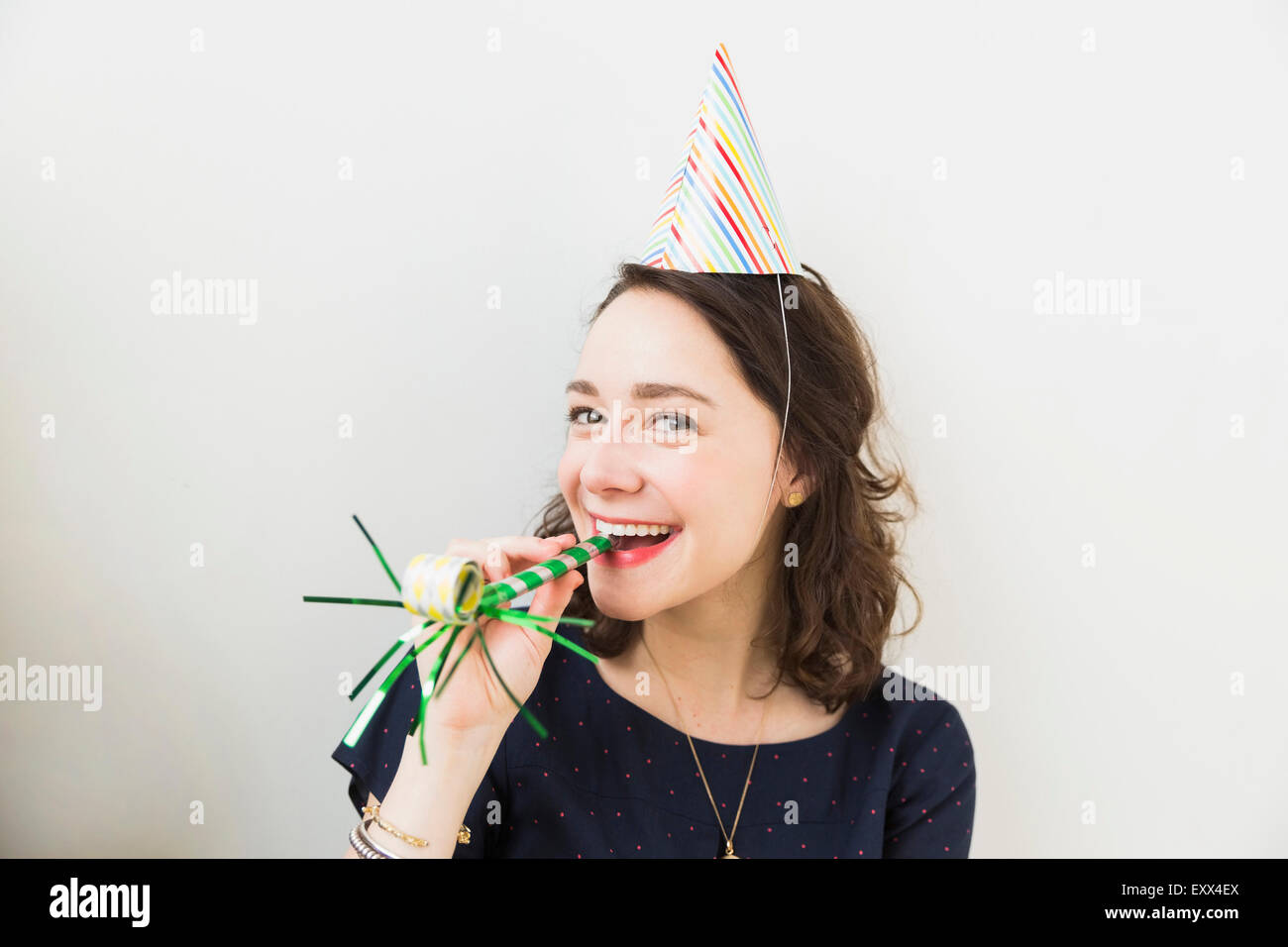 Smiling young woman with party horn blower - Stock Image