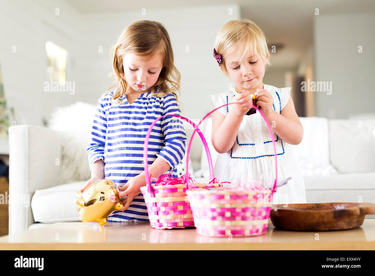 Girls (2-3, 4-5) opening candies - Stock Image