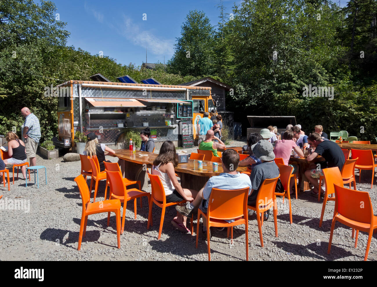 Customers dining outdoors at the Tacofino food truck, a popular takeout restaurant in Tofino, BC. - Stock Image