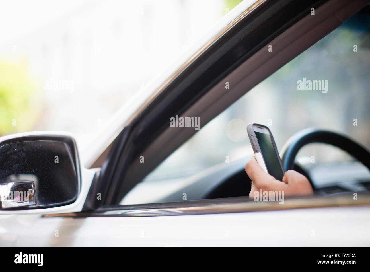 Hand of businessman using smartphone at car window - Stock Image