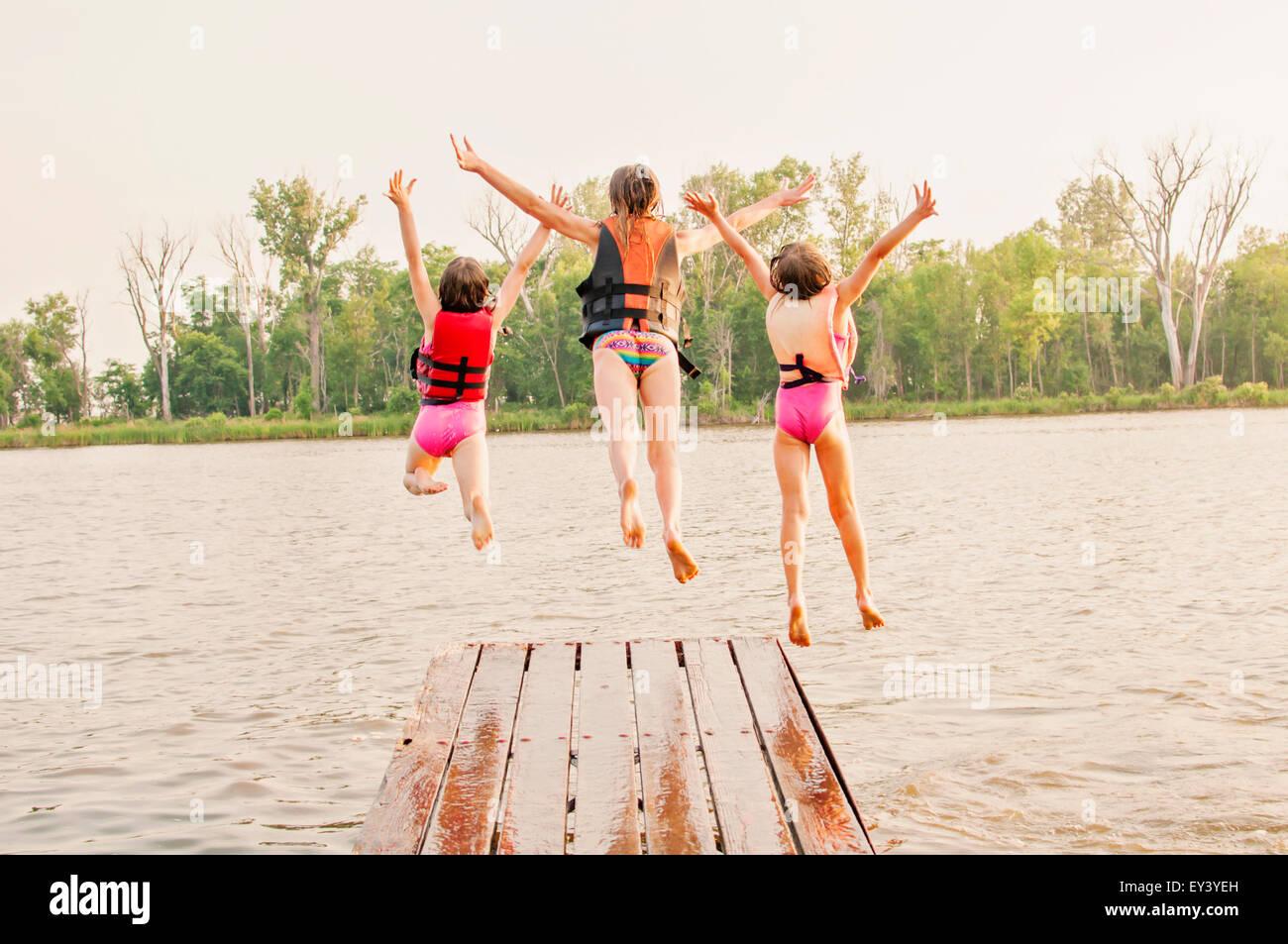 Three girls jump off dock into lake - Stock Image