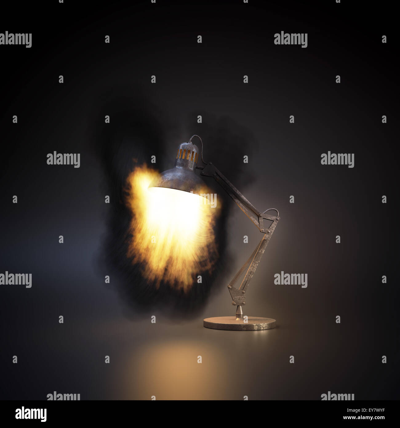 Fire blazing from a desk lamp - Stock Image