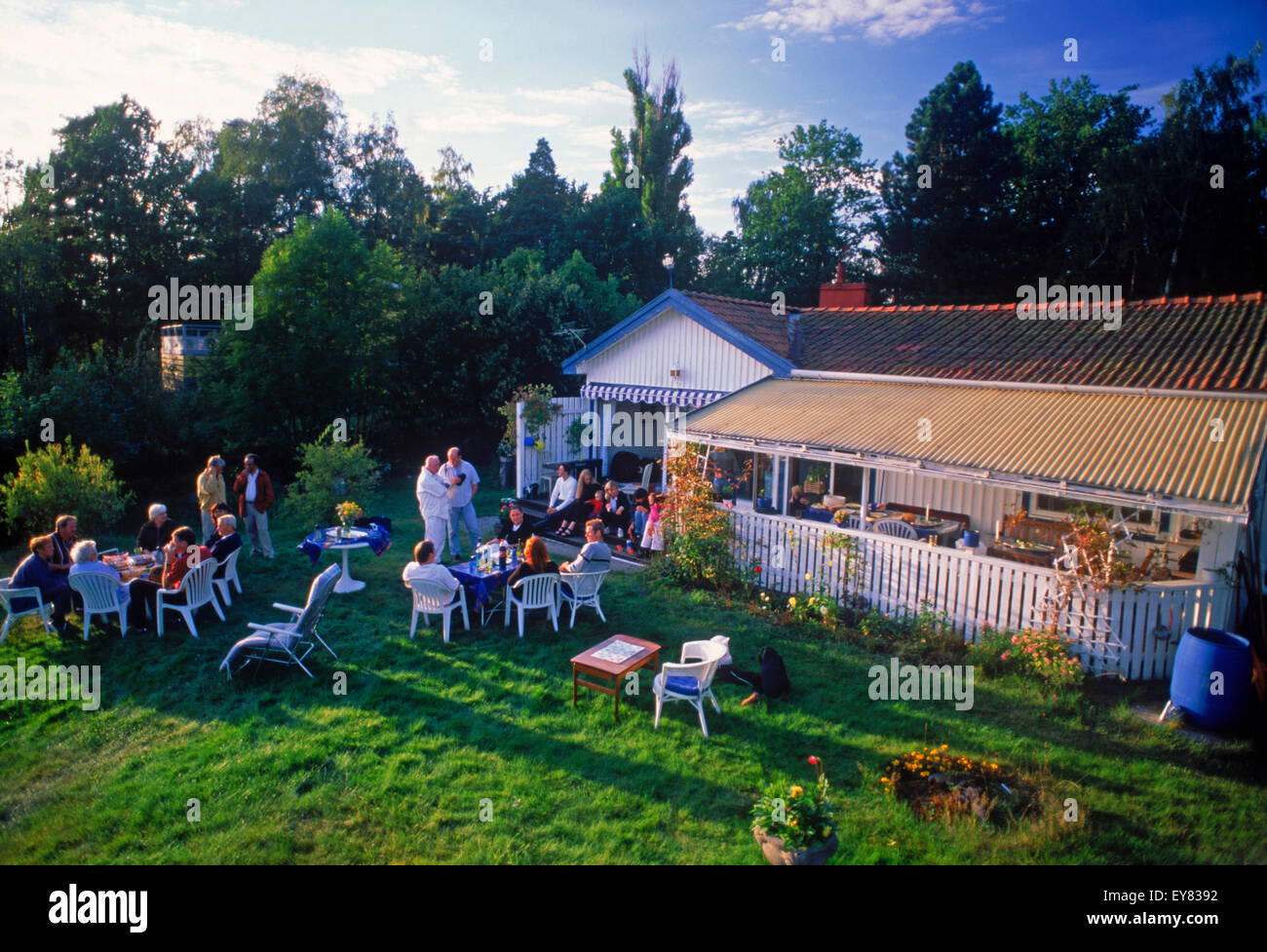 Friends sharing food, coffee and conversation at summer house on Tranholmen island in Stockholm Archipealgo in Baltic - Stock Image