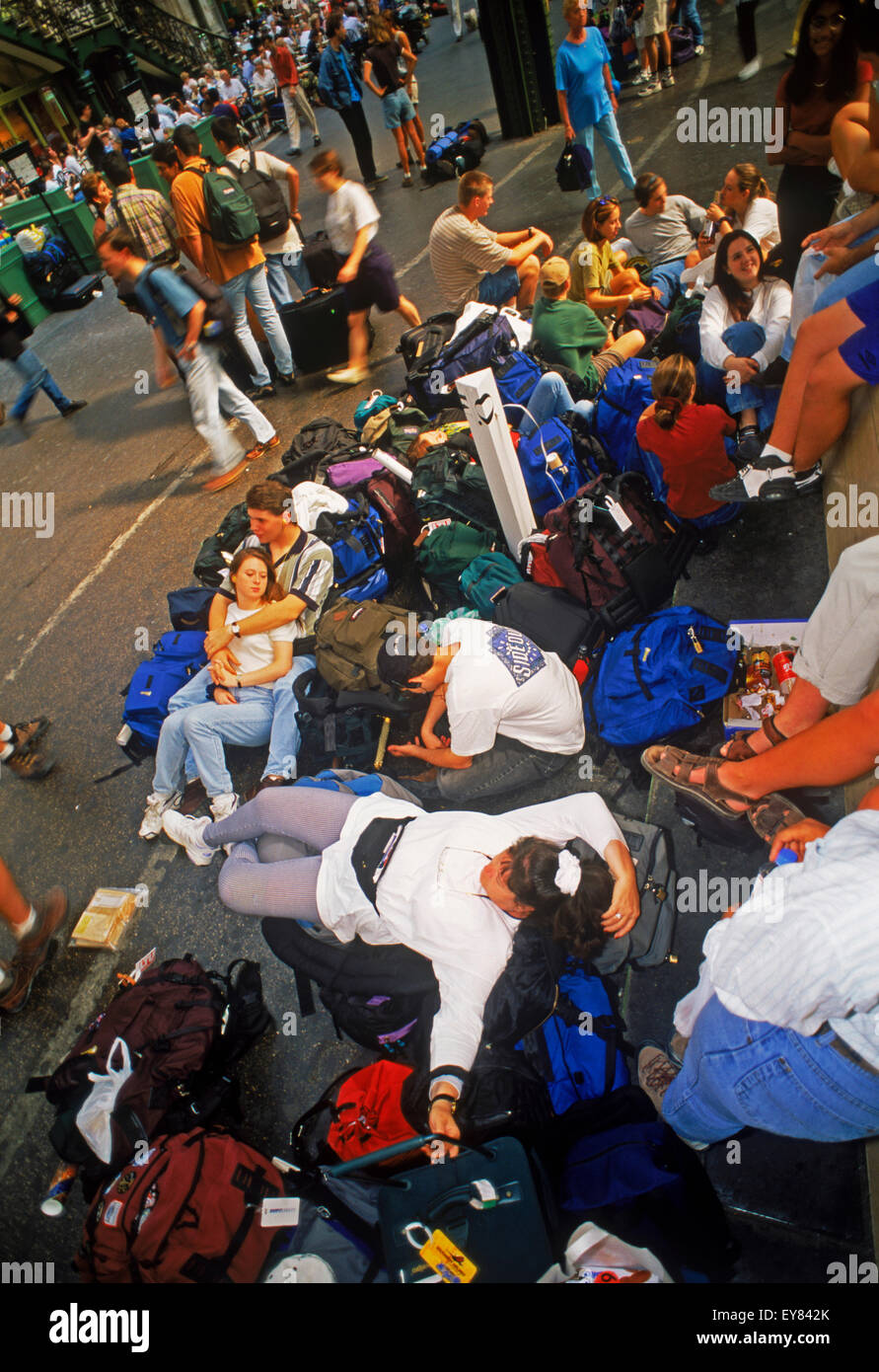 International backpackers waiting in train station in Europe - Stock Image
