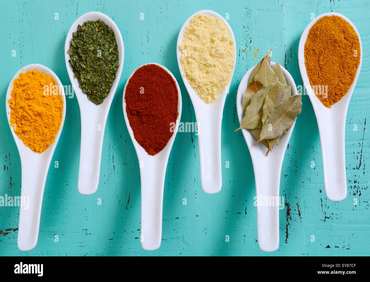 Colorful cooking spices and herbs in white spoons on vintage aqua ...