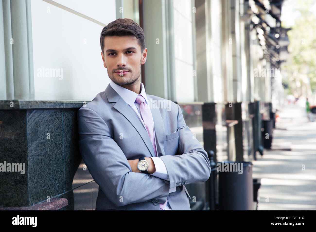 Portrait of a handsome businessman with arms folded standing outdoors in the city - Stock Image
