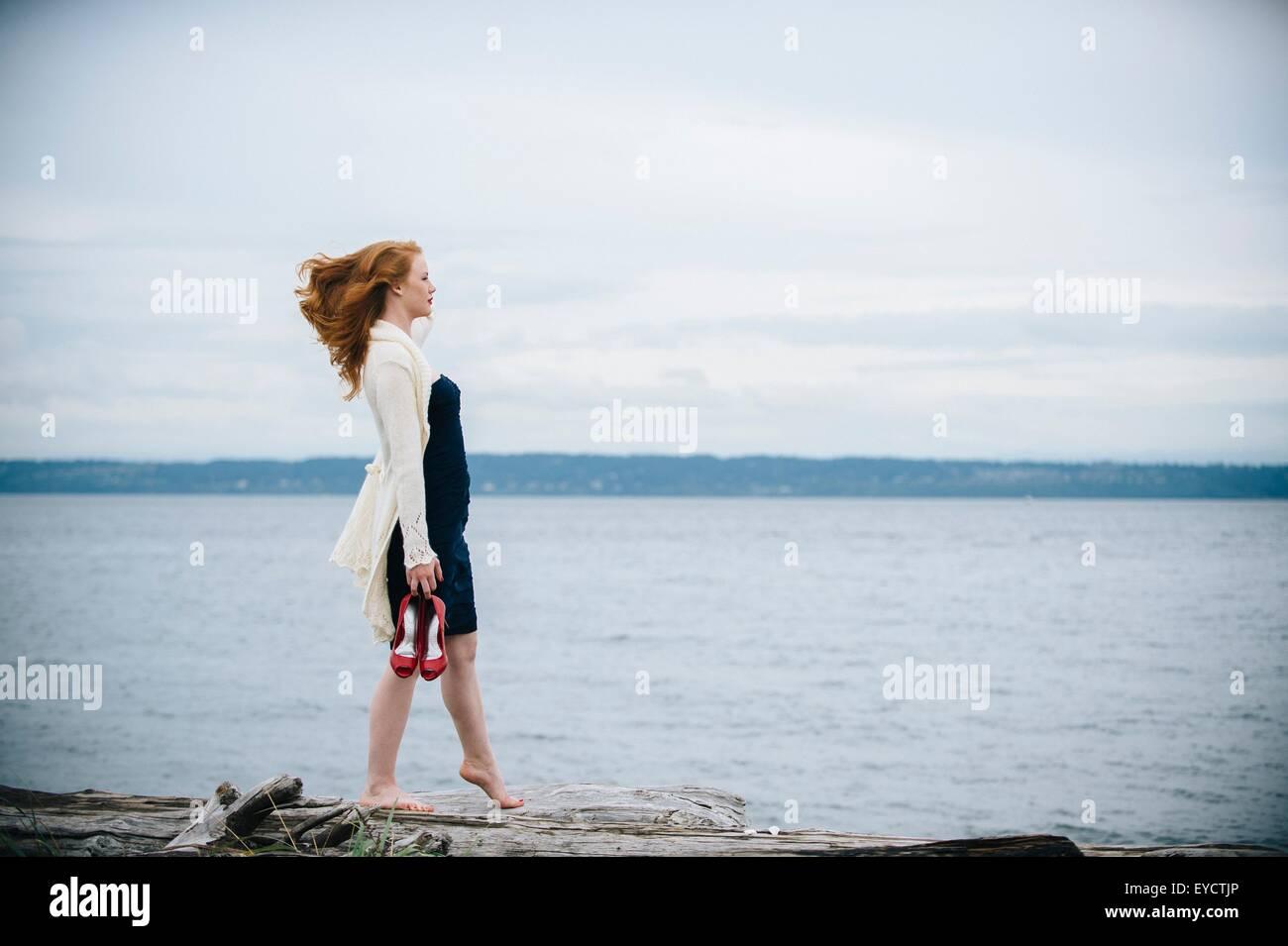 Young woman on beach looking out to sea, Bainbridge Island, Washington State, USA - Stock Image