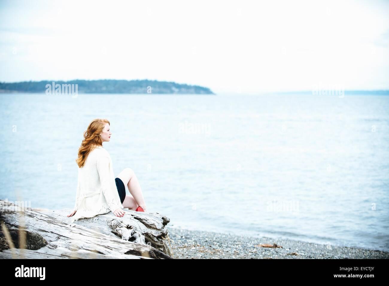 Young woman sitting on beach looking out to sea, Bainbridge Island, Washington State, USA - Stock Image