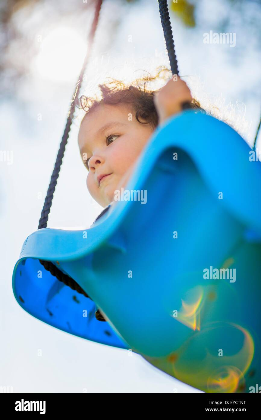 Young girl on playground swing, low angle view - Stock Image