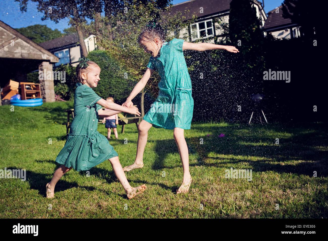 Two children in school summer dresses, running through a water sprinkler. - Stock Image