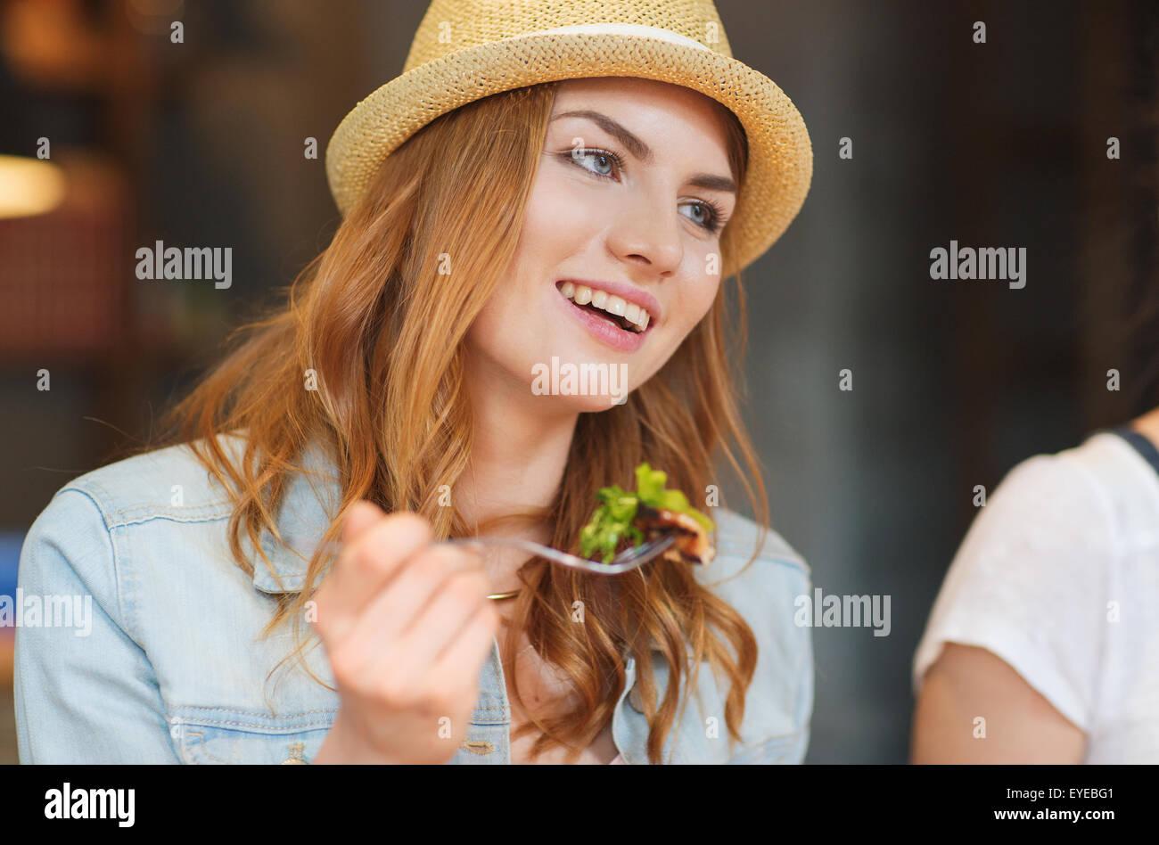 happy young woman eating salad at bar or pub - Stock Image