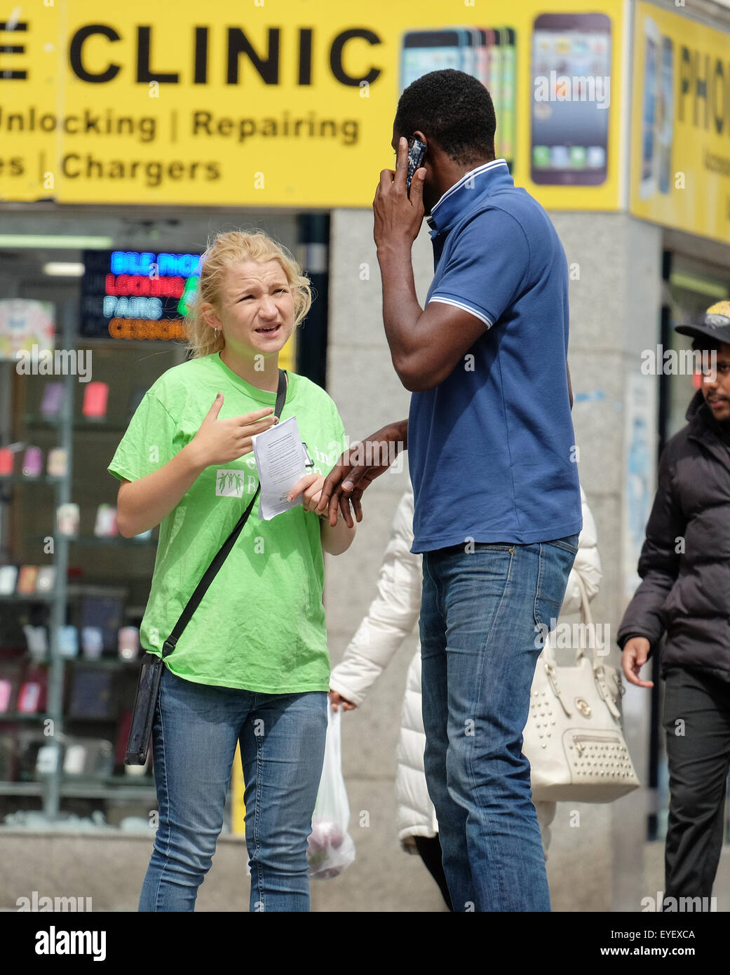 A charity chugger stopping a pedestrian on the street in Southampton - Stock Image
