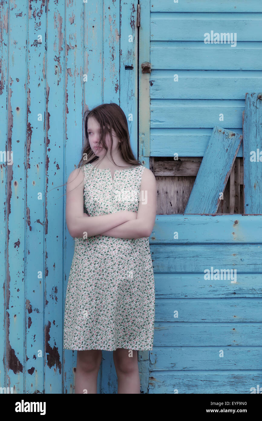 a girl in a floral dress is standing in front of a blue wooden wall - Stock Image