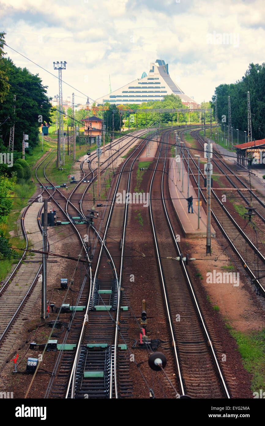 The rails of the railway station in the city of Riga and the National Library Castle of Light - Stock Image