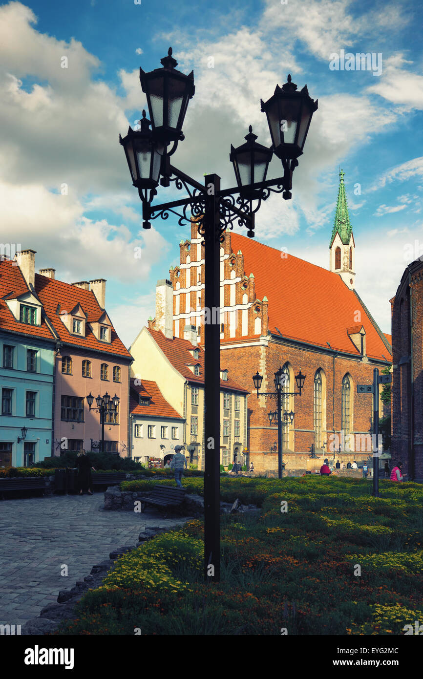 Street lamp in a square in the center of Riga in the summer on a background of old houses and flowers - Stock Image