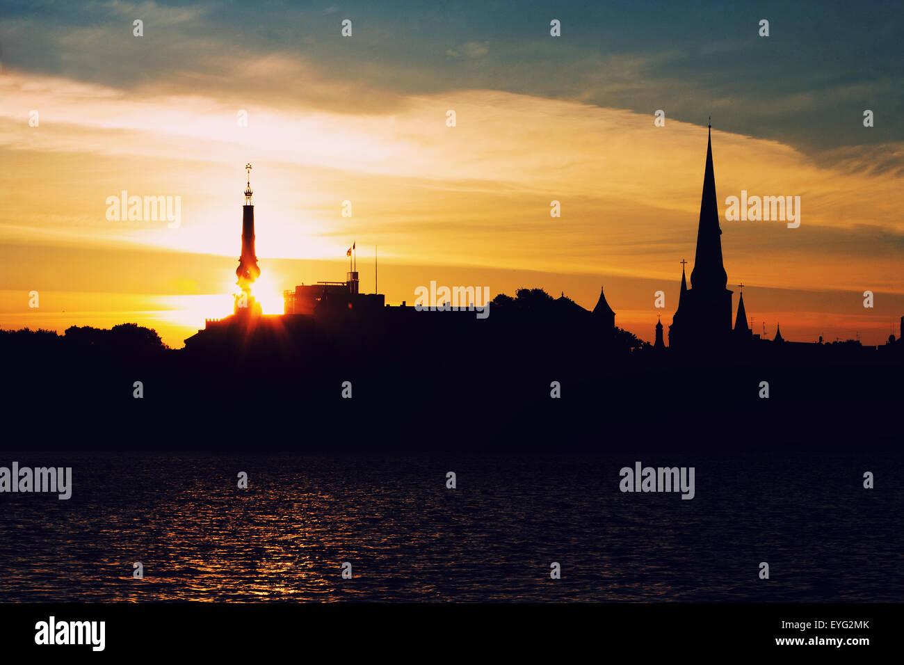 Latvia. Riga. Sunrise over the tower of the palace of President of Latvia on the Daugava River - Stock Image