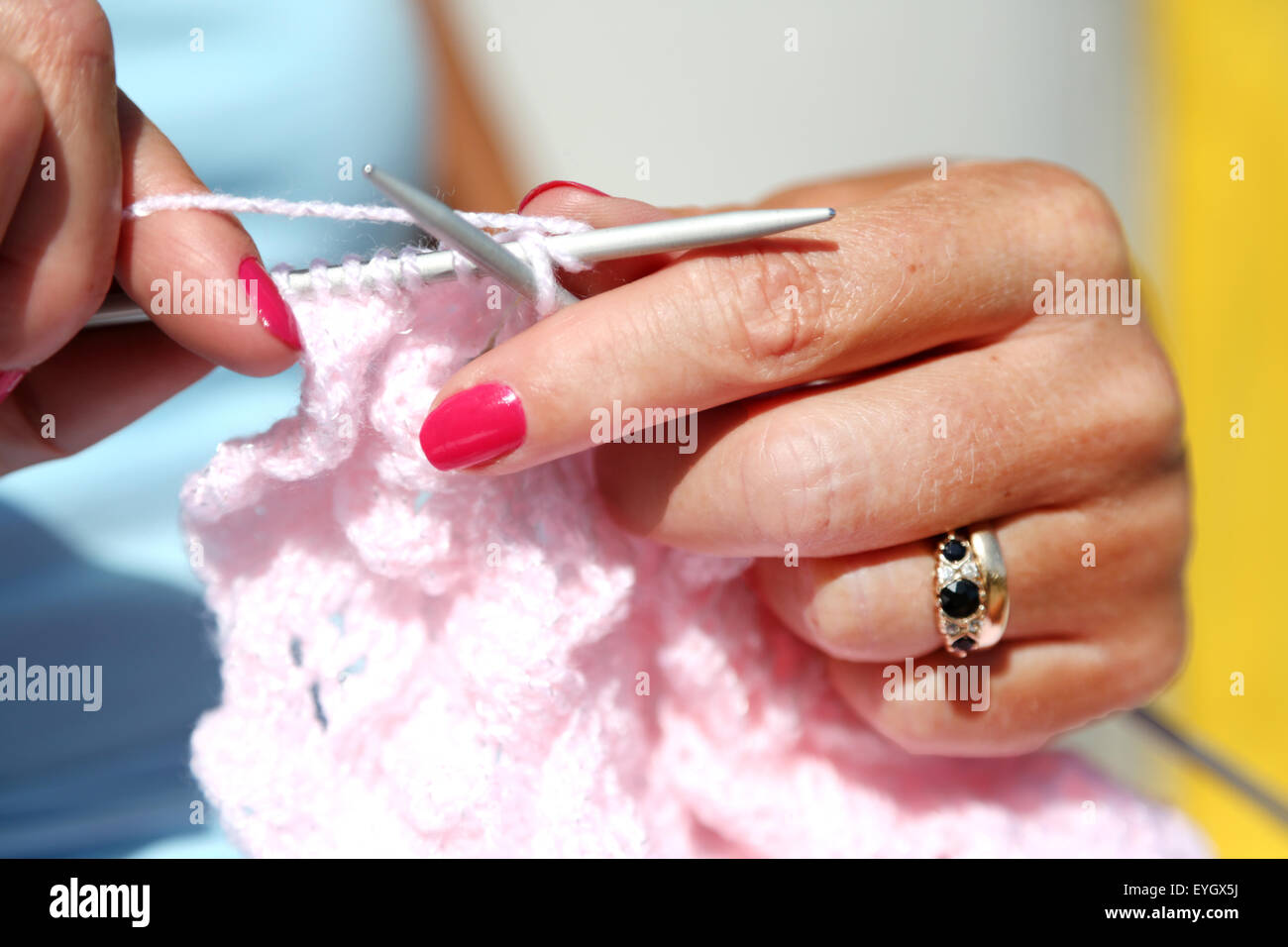 A woman using knitting needles to knit a pink woollen cardigan using a purl stitch - Stock Image