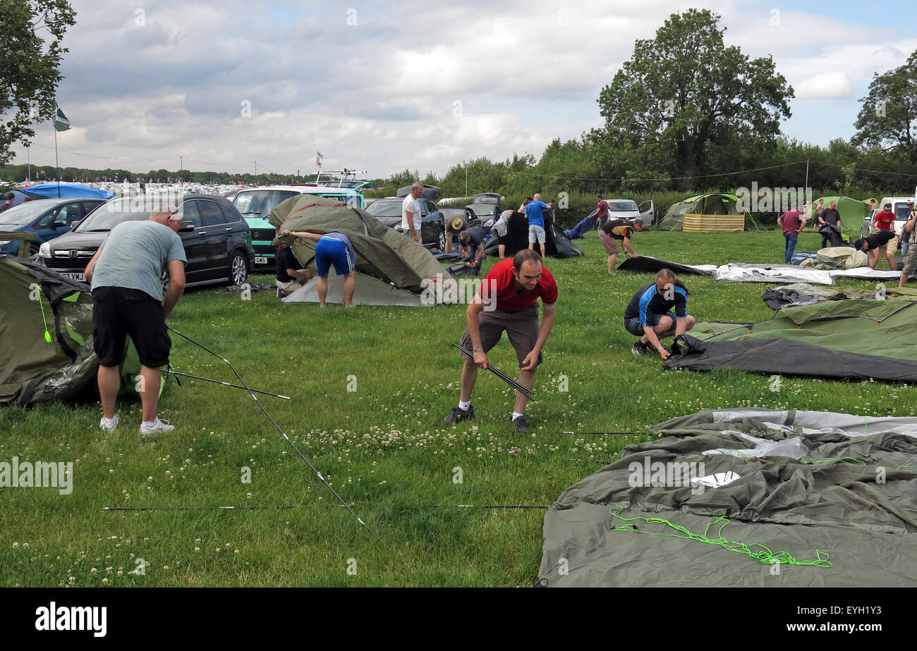 erecting,grass,camp,camping,campsite,sunshine,sun,summer,tent,men,women,males,females,building,knowhow,know,how,practical,skills,skill,Silverstone,Glasto,Random people,putting up tents,in a field,Putting up,GoTonySmith,Buy Pictures of,Buy Images Of