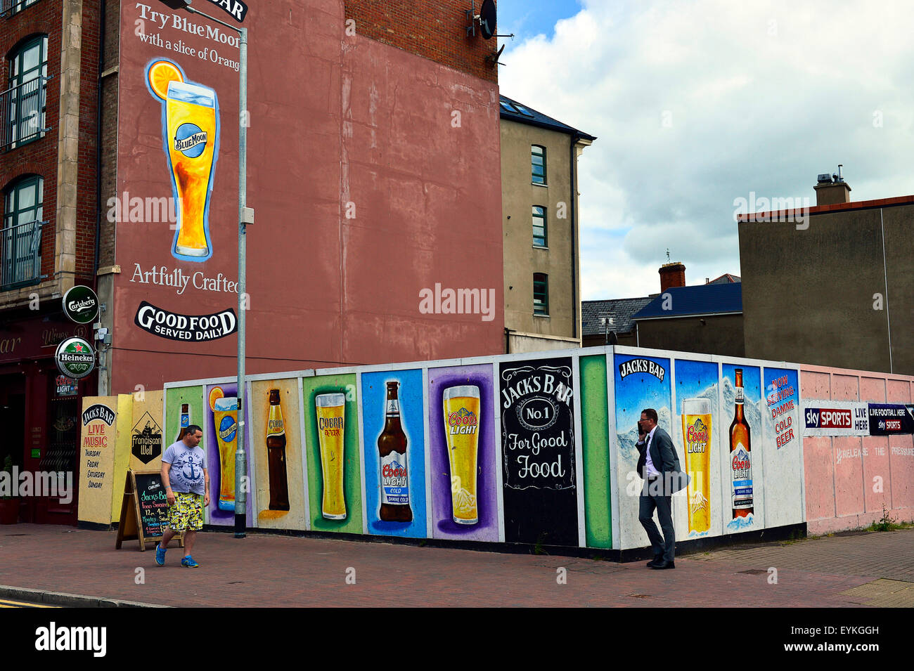 People walking past billboards advertising alcohol outside a pub in Londonderry (Derry), Northern Ireland - Stock Image