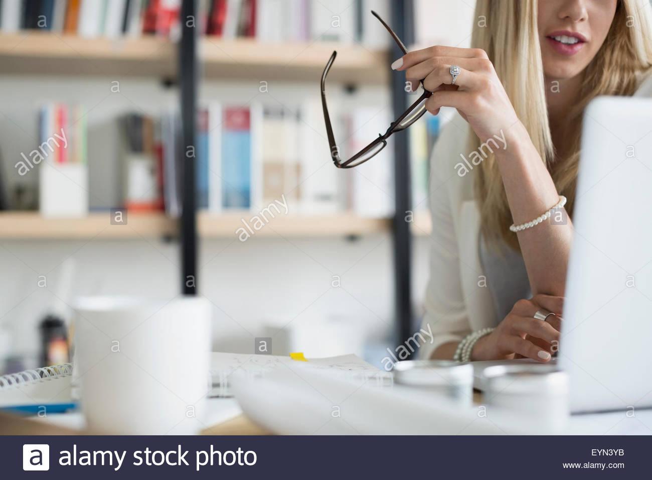 Architect holding eyeglasses using laptop - Stock Image