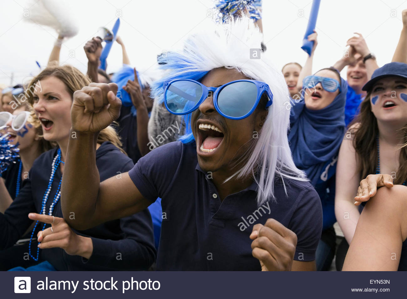 Enthusiastic fan in oversized blue sunglasses cheering - Stock Image