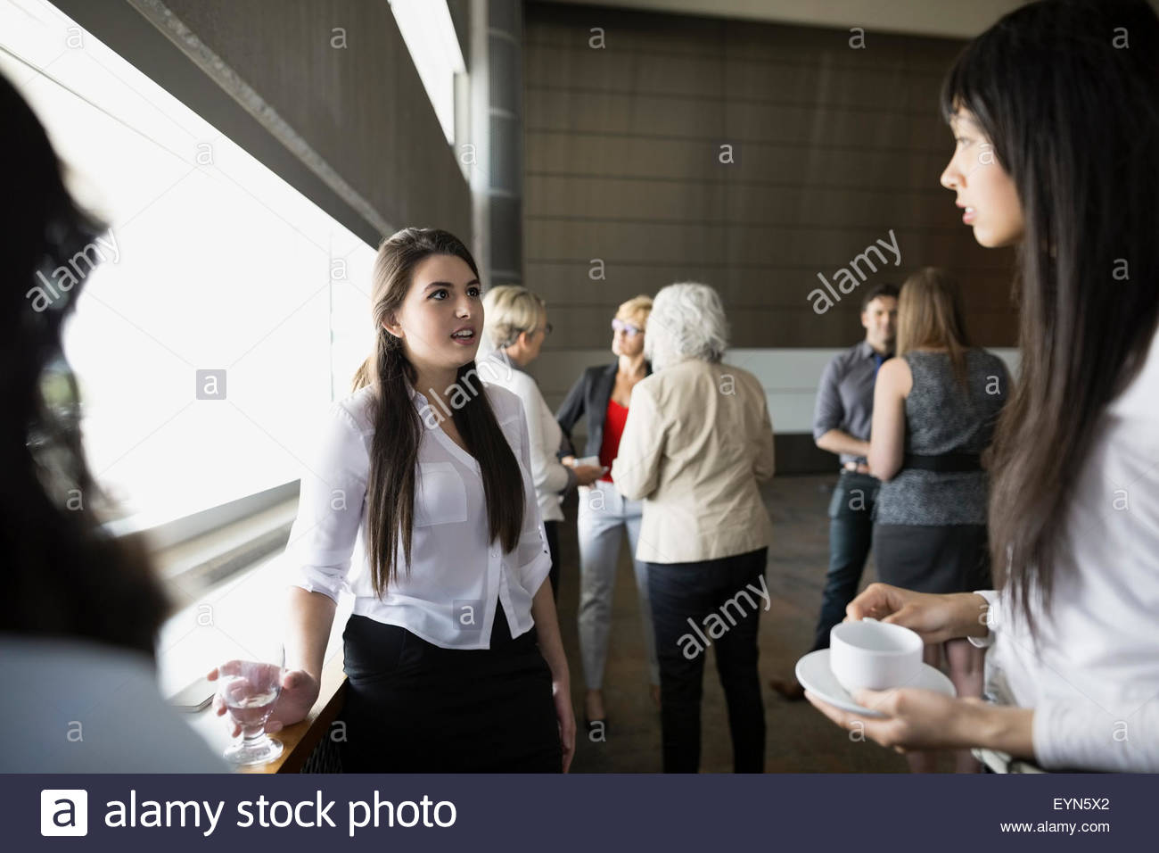 Women socializing in auditorium - Stock Image